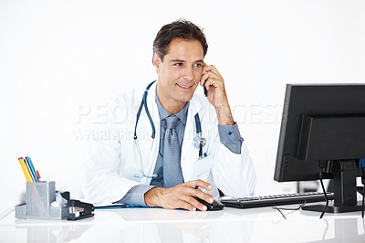 Buy stock photo Mature male doctor busy working at his desk speaking on mobile phone