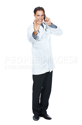 Buy stock photo Full length of mature doctor gesturing ok sign while using mobile phone isolated on whote background