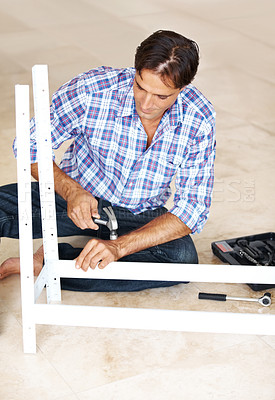Buy stock photo Manual worker working on a metal rack with a hammer in his workshop