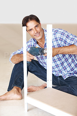 Buy stock photo Happy man assembling a shelf