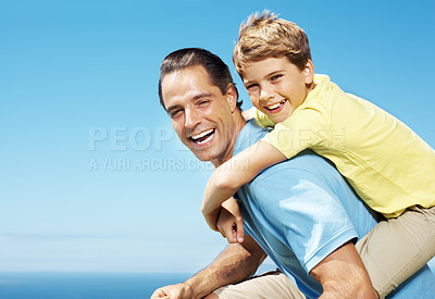 Buy stock photo Portrait of happy father giving piggyback ride to his sweet son outdoors against sky