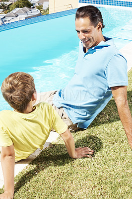 Buy stock photo Smiling mature man sitting along with his small son near water pool - Summer vacations