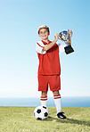 Smiling little footballer holding winners trophy - Outdoors