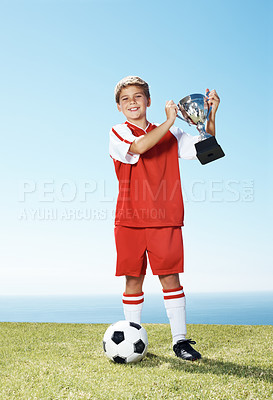 Buy stock photo Portrait of a smiling little boy holding a winning trophy and soccer ball - Outdoor