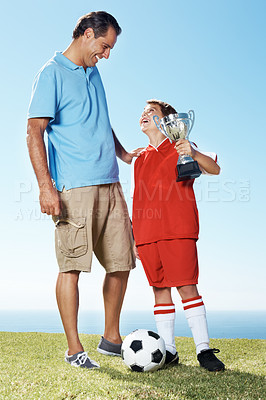 Buy stock photo Portrait of a small young boy looking at his father while holding a winning trophy - Outdoor