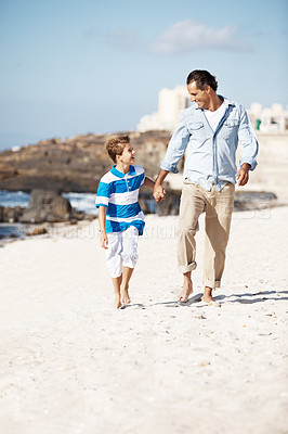 Buy stock photo Portrait of caring father and his son holding their hands together and walking on the beach