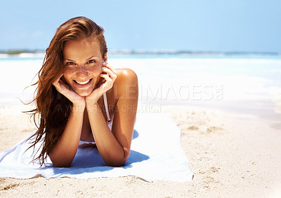 Buy stock photo Portrait of young woman smiling beautifully at you while relaxing on beach alongside copyspace