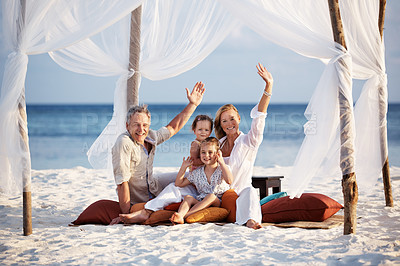 Buy stock photo Portrait of beautiful family sitting under beach tent waving at you
