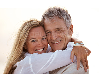 Buy stock photo Closeup portrait of a romantic mature couple smiling at you while embracing lovingly