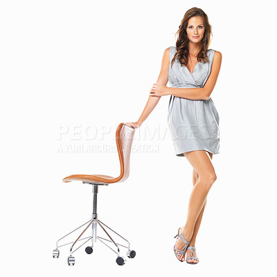 Buy stock photo Full length of elegant young woman standing with hand on chair against white background