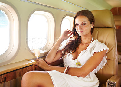 Buy stock photo Portrait of a beautiful woman enjoying a glass of champagne in the cabin of a private jet