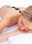 Closeup of a female pampering herself with a stone massage therapy