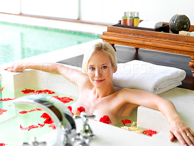 Buy stock photo Portrait of pretty young woman relaxing in bath tub with red flower petals