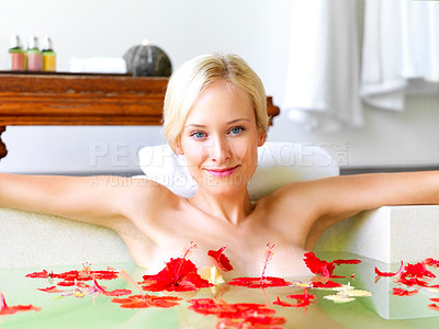 Buy stock photo Portrait of attractive young lady in bath tub with red flowers petals