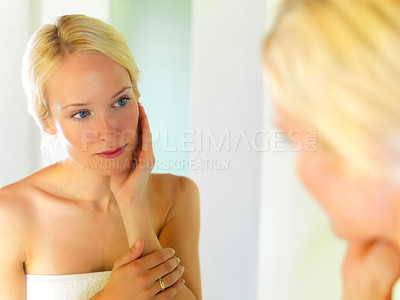 Buy stock photo Beautiful young female looking at her face in a mirror