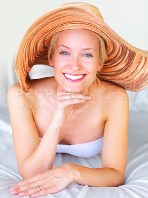 Buy stock photo Portrait of sexy young woman in a bikini wearing a hat lying on a bed