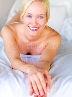 Buy stock photo Attractive young lady lying on bed looking happy