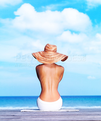 Buy stock photo Rear view of sexy topless woman sitting on a porch facing the sea