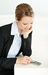Young Caucasian business lady looking at her mobile phone