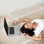 Top view of a lovely female lying on the floor besides a laptop