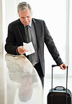 Senior man with his luggage, reading a receipt at check in