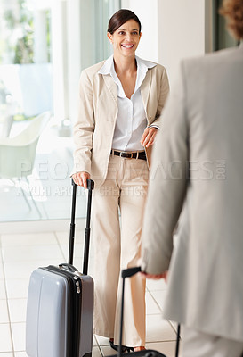 Buy stock photo Mature businesswoman smiles at her male associate at hotel reception with baggage