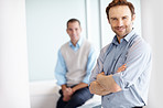 Happy business man with hands folded and a man in blurred