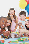 Cute little kids enjoying the birthday cake at a party