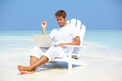 Buy stock photo Portrait of young man working on laptop while relaxing on beach