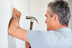 Mature man hammering a nail into the wall