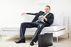 Middle aged business man sitting on sofa and looking at necktie