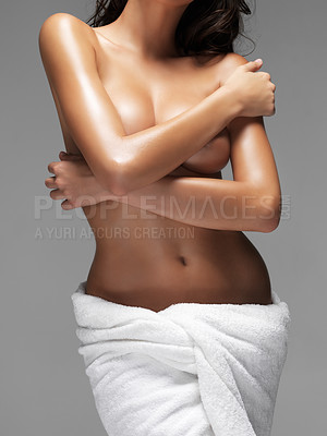Buy stock photo Mid section of alluring woman in towel covering her breasts with hands