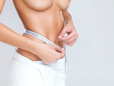 Buy stock photo Mid section of sexy young woman with perfect body measuring her waist