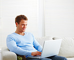 Man sitting on couch using laptop computer
