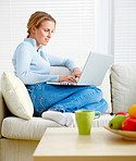 Pretty blond relaxing on sofa and using laptop
