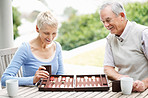 Cheerful senior couple enjoys a game of backgammon