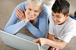 Grandson showing something to smiling grandmom on a laptop