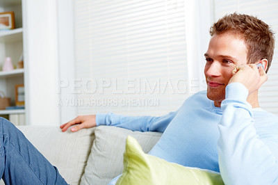 Buy stock photo Young man using a mobile phone in his house