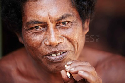 Buy stock photo A Thai man pauses to smile at something while smoking a handrolled cigarette