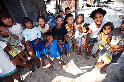 Buy stock photo A group of underprivileged children standing in front of a shack