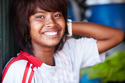 Buy stock photo A close-up of a relaxed and happy Thai girl smiling and leaning against a wall