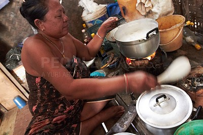 Buy stock photo A Thai woman sitting on the floor cooking food