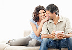 Happy cosy mature couple on couch by lots of copyspace