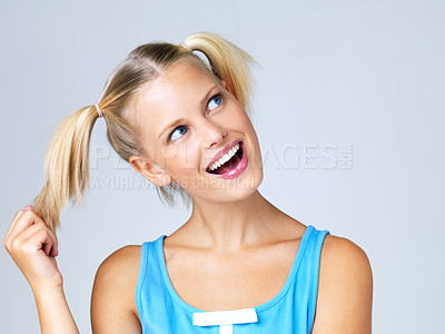 Buy stock photo Portrait of attractive young blonde in pigtails looking sideways and playing with her hair