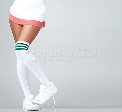 Buy stock photo Close up of woman's legs in a skirt and long socks with trainers on with copyspace