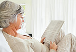 Senior woman reading something interesting newspaper on bed