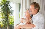 Cute retired couple with arms around by the window