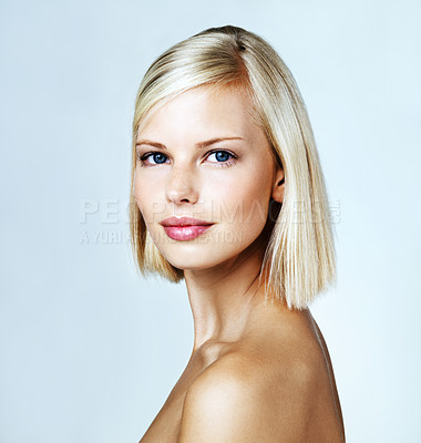 Buy stock photo Stunning young blond woman looks at you while isolated on light blue