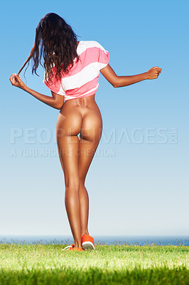 Buy stock photo Rear view of a young ethinc woman undressing outdoors