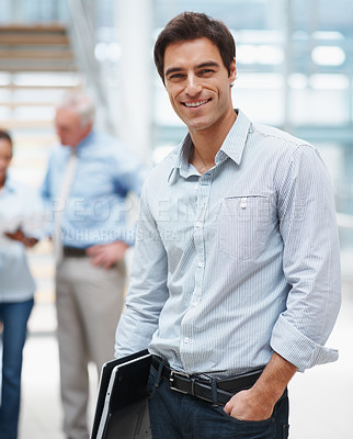 Buy stock photo Portrait of a happy young business man with colleagues in the background